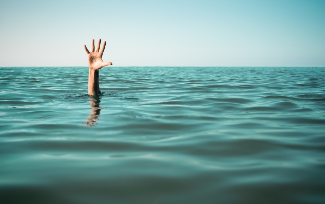 Hand in sea water asking for help. Failure and rescue concept.