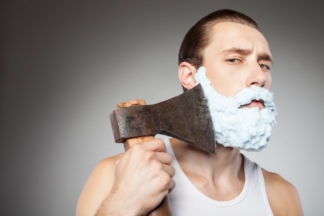 Attractive young bearded guy shaves with hatchet